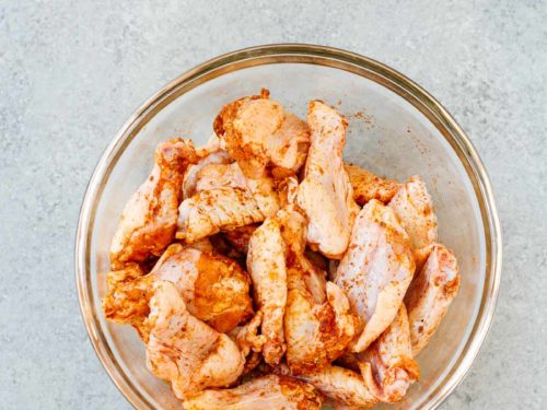 overhead view of a glass bowl containing raw chicken wings