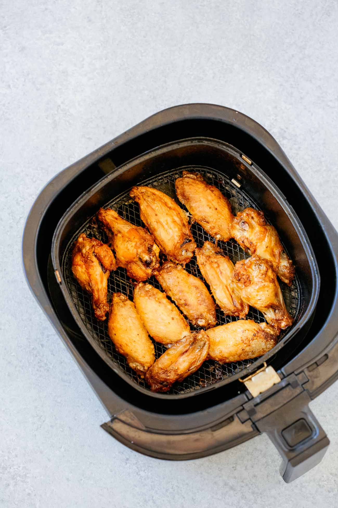Air fryer basket with chicken wings.