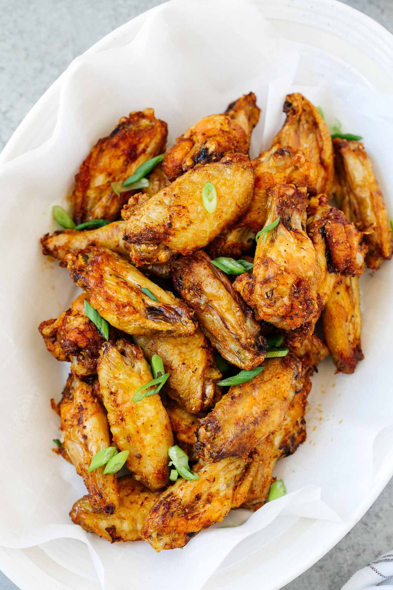 A white plate with chicken wings and green onion garnish.