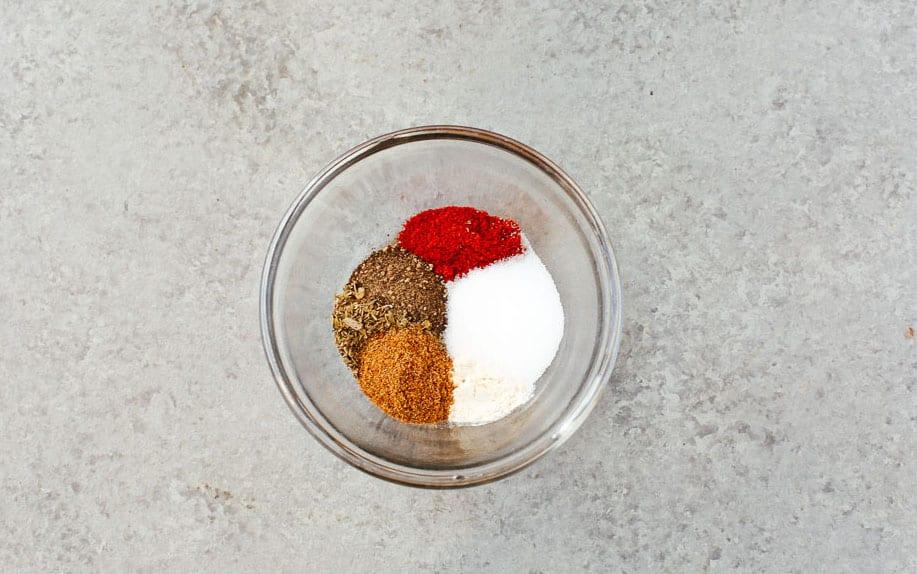 A bowl with dried oregano, paprika, garlic powder, ground coriander, cumin, salt, and black pepper.