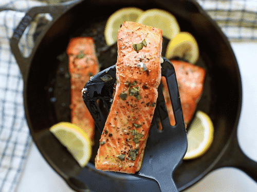 overhead view of a cast iron skillet containing salmon