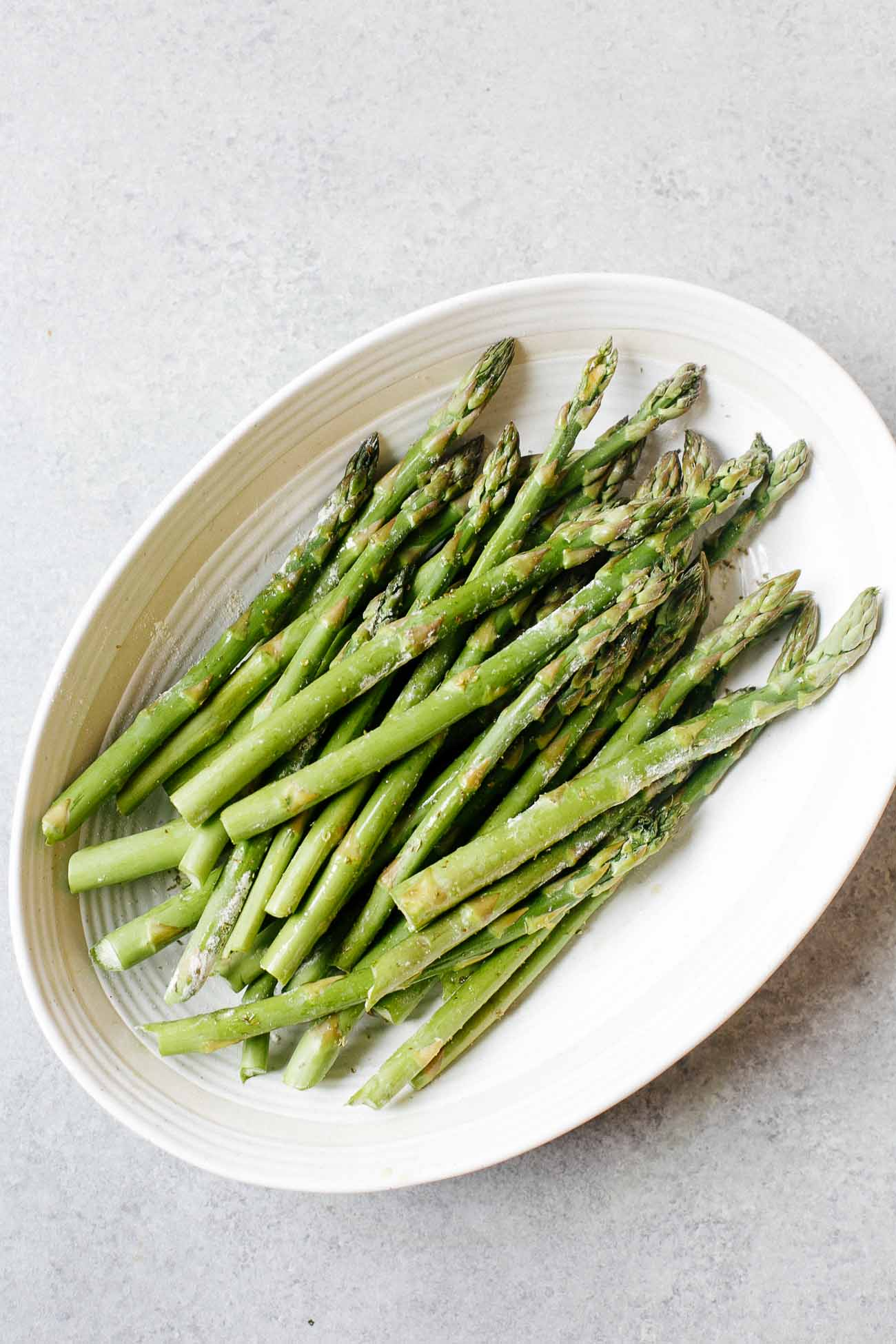 overhead view of asparagus in a casserole white dish