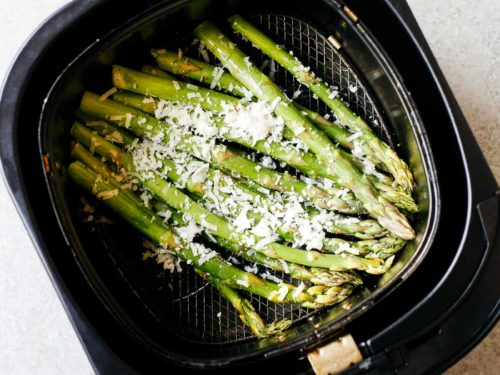 overhead view of asparagus inside of an air fryer