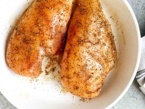overhead view of seasoned chicken breast on a white place