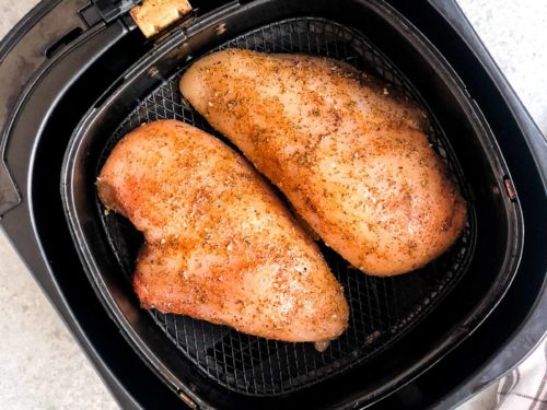 overhead view of 2 chicken breasts inside of an air fryer