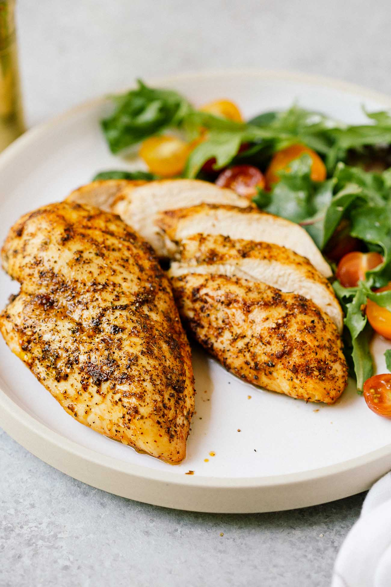 A plate with two air fryer chicken breasts.