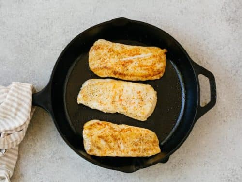 overhead view of cooked halibut fish in a cast iron skillet