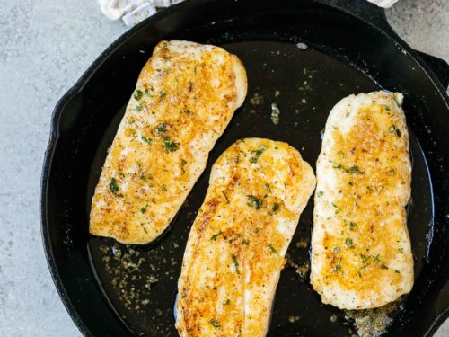 overhead view of garlic butter halibut fish in a cast iron skillet