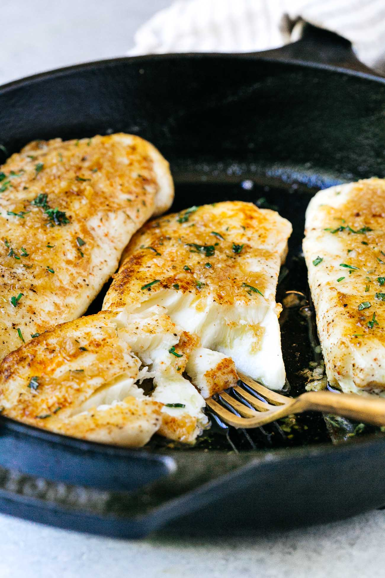 closeup of flaky garlic butter halibut fish in a cast iron skillet