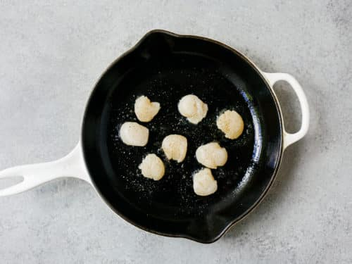 overhead view of raw scallops in a cast iron skillet