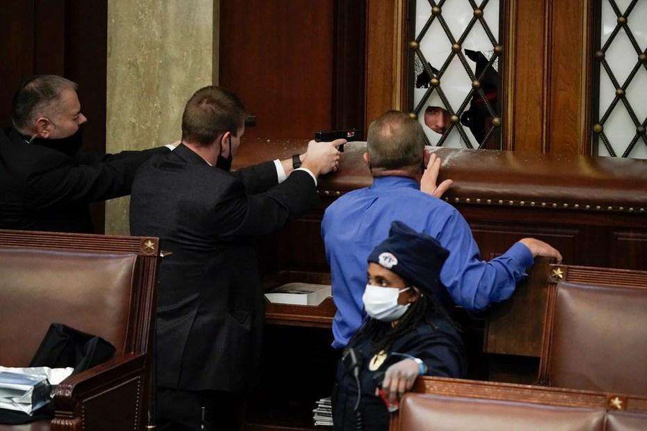 La Policía apunta con sus pistolas a los manifestantes que intentan entrar al Capitolio.