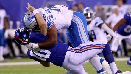 EAST RUTHERFORD, NJ - SEPTEMBER 18:  Eli Manning #10 of the New York Giants gets tackled by Cornelius Washington #90 of the Detroit Lions in the fourth quarter during their game at MetLife Stadium on September 18, 2017 in East Rutherford, New Jersey.  (Photo by Al Bello/Getty Images)