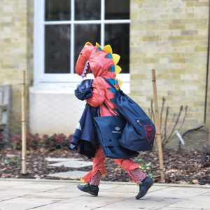 A child walking to school with their backpack, dressed as a dragon.