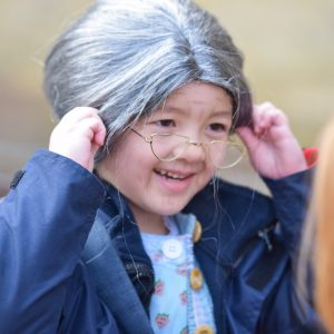 A small girl dressed up aas an old woman, with a grey wig and wire frame glasses.