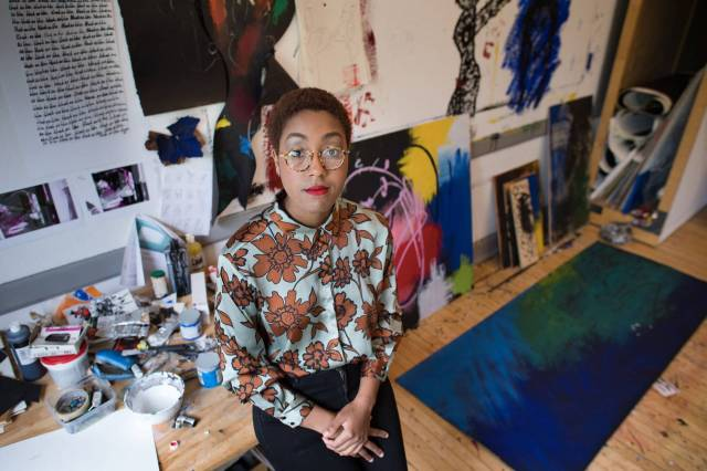 Imani Ford in front of her paintings and artwork