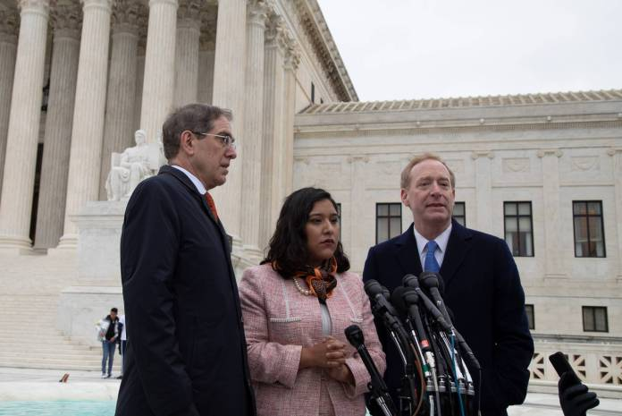 Christopher Eisgruber, Brad Smith and Maria Perales Sánchez on the steps of the Supreme Court building in Washington, D.C.