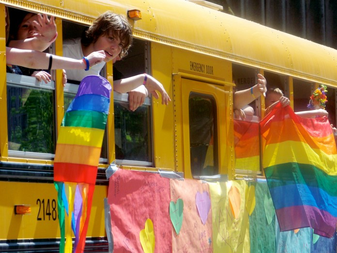 Children hanging rainbow flags out of a bus window