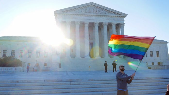 A photo of a man waving an LGBTQ+ rainbow flag outside the Supreme Court