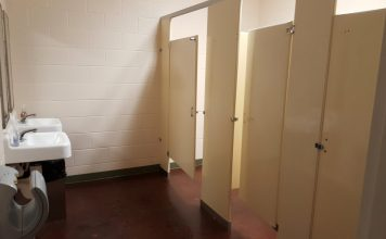 An image of three bathroom stalls, with one stall door open.