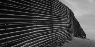 A black-and-white image of the U.S.-Mexico border wall fence.