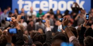 A photo of reporters taking pictures of the Facebook logo with their phones.