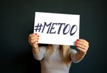 An anonymous woman holding up a sign that says #MeToo
