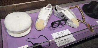 Image of a hat, eye patch, tennis shoes, gold necklace, and top hat displayed in glass case