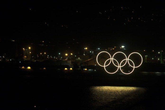 Photo of illuminated Olympic rings against dark city