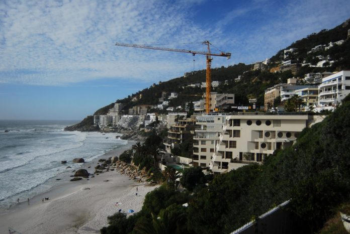 Photo of the coast of Cape Town showing high rise buildings and a crane