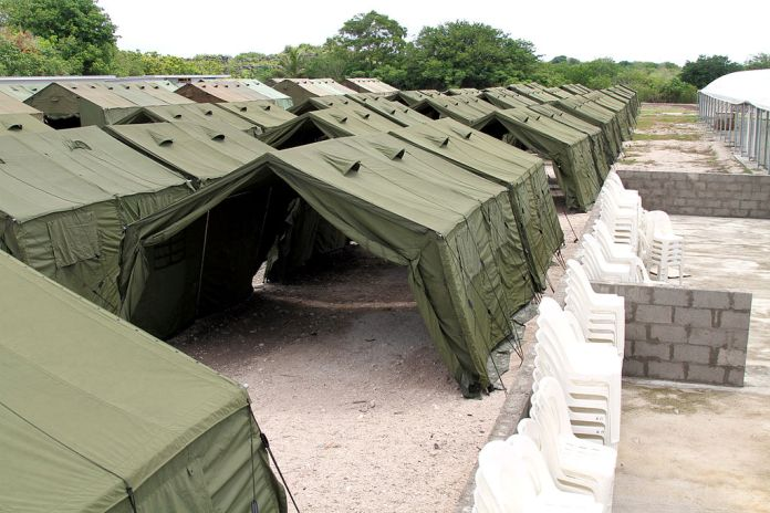 Photograph of a long row of dark green tents