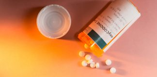 photograph of a pill bottle with pills spilling out