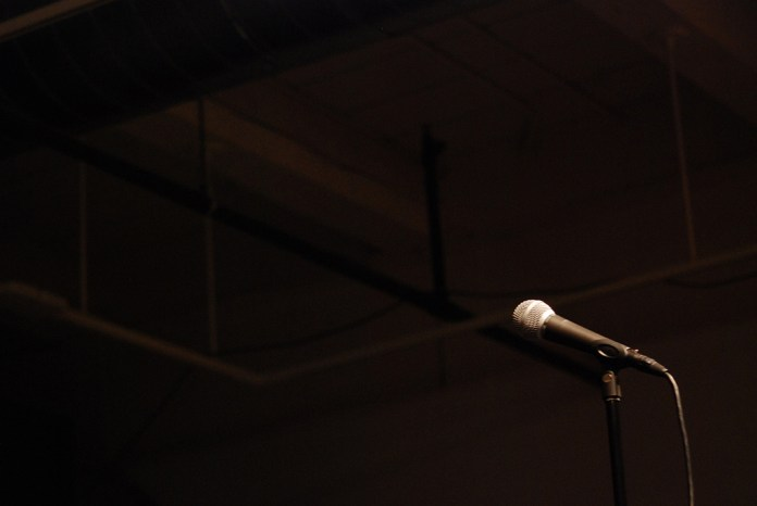 photograph of a microphone and a dark background