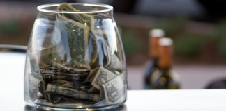 Photograph of a clear glass jar with dollars in it