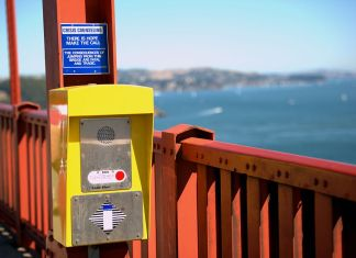 "Photo of a sign at the Golden Gate Bridge that says ""Crisis counseling - There is hope - Make the call - The consequences of jumping from this bridge are fatal and tragic""."