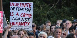 """Photograph of a rally with a person holding a sign saying """"Indefinite Detention is a crime against humanity"""""""