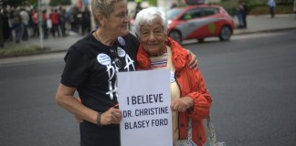 "Two women holding a sign that says ""I believe Dr. Christine Blasey Ford"""