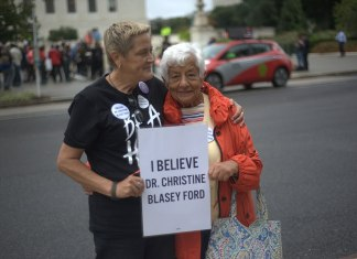 """Two women holding a sign that says """"I believe Dr. Christine Blasey Ford"""""""