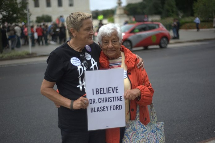 Two women holding a sign that says