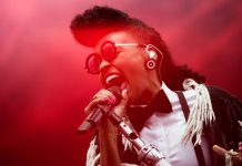 Photograph of singer Janelle Monáe holding a microphone