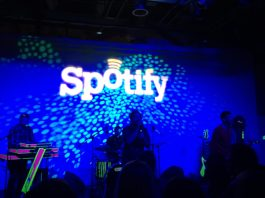 Photo of the Spotify logo behind a band on a stage
