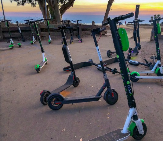 Photograph of several dockless scooters on an area of pavement with a sunset sky in the background