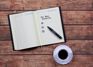 """Photograph of an open notebook with a pen on it; written on the notebook is """"New Years Resolutions"""""""