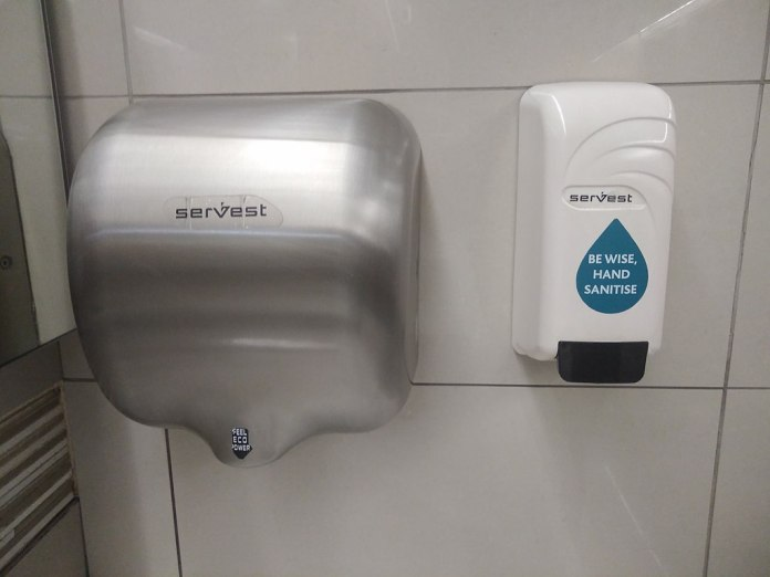 Photograph of a hand drier and a hand sanitizer dispenser attached to a tiled wall