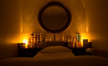 Photo of a lowlit room with candles and a mirror and a bed