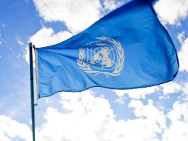 Photo of the UN flag flying against a blue sky with white clouds