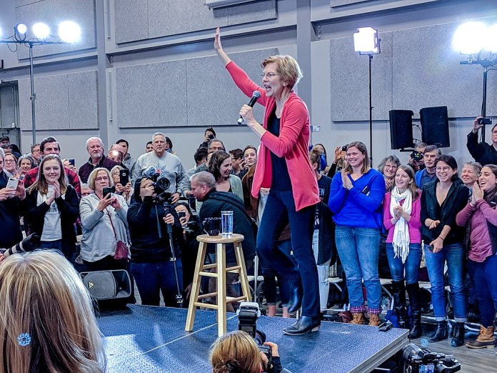 Elizabeth Warren standing on a podium with a stool, speaking to a crowd while holding a microphone