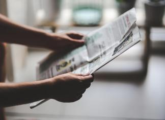 Photograph of a newspaper held up by two arms