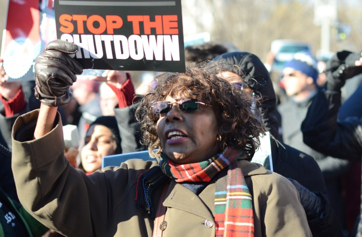 "A woman holding a sign that says ""stop the shutdown"""