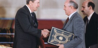 Photograph of Reagan and Gorbachev shaking hands and holding a document