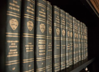 "Photograph of a bookshelf of uniform ""harvard classic"" books; visible titles are Don Quixote and The Aeneid"